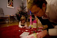 Dad and daughter build a toy castle which she received for Christmas, Kalmar, Sweden.