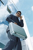 Businessman carrying briefcase using cell phone outside office building