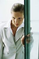 Businesswoman entering building, hesitating at doorway