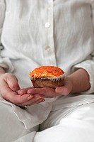 A woman holding a muffin close_up Sweden.