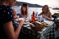 Scandinavian family having dinner Greece.