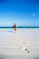A woman walking on a beach Zanzibar.