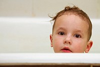 A portrait of a little boy looking over the edge of the bathtub, directly at the camera