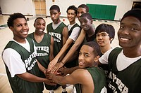 Basketball players touching ball in huddle