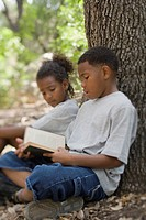African boy and girl reading book against tree