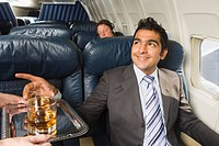 Middle Eastern man taking drink from tray on private jet