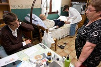 Home consultation, Nord, France. Visit at the place of a patient affected by liver cancer in terminal stage. A nurse ministering to the patient is als...