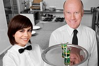 Waiter and a waitress standing in the kitchen and smiling