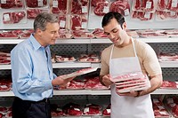 Sales clerk giving meat to a man in a supermarket