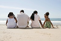 African american family sitting on a beach