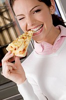 Female chef eating a slice of pizza