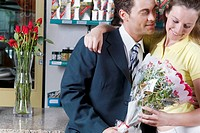 Couple holding a bouquet of flowers in a flower shop