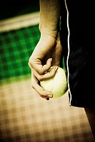 Mid section view of a person holding a tennis ball