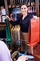Woman holding shopping bags at checkout counter
