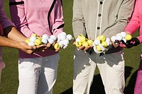 Mid section view of four friends holding golf balls, Biltmore Golf Course, Coral Gables, Florida, USA