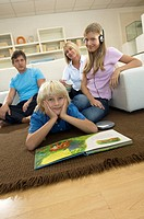 family in livingroom, brother and sister with book and cd player