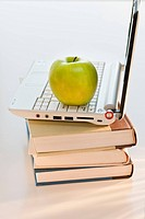 Apple on laptop and books