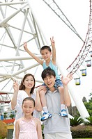 Young family with two children standing near ferries wheel and gesturing with smile, Family, Leisure Activities