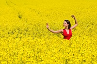 Young woman meditating in a field of rape