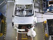 Worker Assembling Car On Production Line