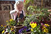 Girl filling pot with soil