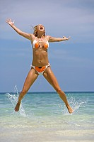 Happy young woman jumping on the tropical beach in Thailand Krabi