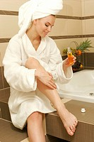 Women with a bathrobe oiling her legs