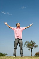 Happy man standing outdoors with arms raised, full length