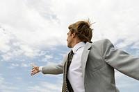 Businessman reaching towards sky