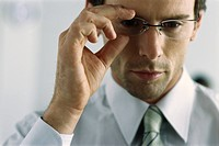 Young businessman adjusting glasses, portrait