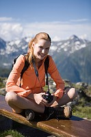 Pretty young woman trekking in the mountains having rest