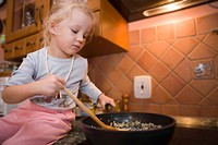Little girl cooking food in a pan