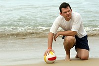 Man mit Volleyball am Strand