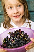 Girl with a bowl of grapes