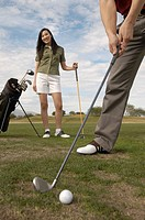 Woman Watching Man preparing to Hit Golf Ball on golf course