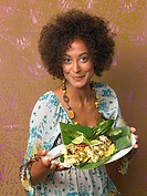 Young woman with spicy fish kebabs in banana leaf