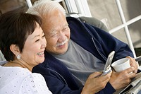 Senior couple using mobile phone outdoors