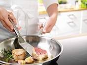 Chef browning pieces of pork fillet in clarified butter
