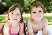Boy and girl lying in backyard portrait close up