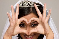 Bride in her 20s draws a heart with her hands at the camera