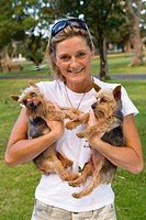 Young woman in park holding dogs to chest, smiling, portrait