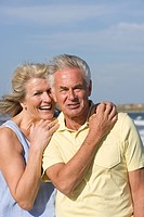 Portrait of senior couple standing on beach