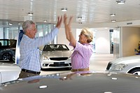 Couple looking at new cars in showroom