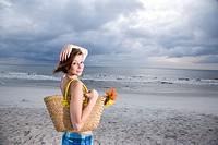 Portrait of young woman standing on beach with handbag and flowers