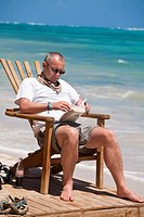 Tourist sitting in chair on beach reading book, Playa del Pablo, Little Corn Island, Corn Islands, Nicaragua