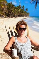 Tourist sitting in chair on beach, Playa del Pablo, Little Corn Island, Corn Islands, Nicaragua