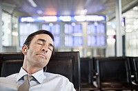 Businessman napping in airport terminal