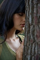 Woman leaning against tree trunk