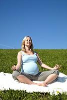 junge schwangere frau macht yoga in der