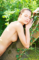 Topless young woman leaning against a tree in a park